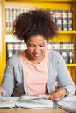 Femme souriant tandis que livre de lecture dans l'université photos libres de droits