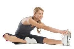 Femme souriant tout en s'étirant pour toucher ses orteils Photo stock