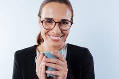 Femme souriante positive appréciant sa boisson Images libres de droits