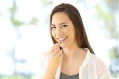 Femme souriante prenant une pilule vous regardant image stock