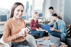Femme sourie agréable tenant une tasse de thé et de se reposer Photos libres de droits