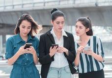 Femme sournoise regardant l'autre téléphone portable de personnes image stock