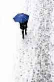 Femme sous le parapluie sur le trottoir neigeux Photographie stock libre de droits