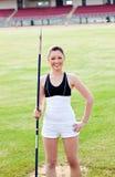 Femme sportif joyeux retenant un javelot dans un stade Image stock