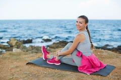 Femme sportive écoutant la musique se reposant sur la plage Images stock