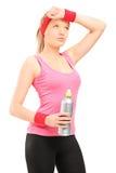 Femme sportive épuisée dans les vêtements de sport tenant une bouteille de l'eau Photographie stock