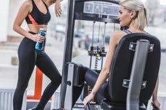 femme sportive attirante établissant avec la machine de gymnase tandis que son associé se reposant avec la bouteille d'eau à côté Photo stock