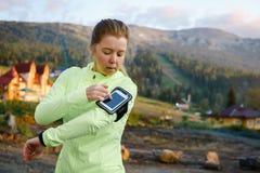 Femme sportive avec l'ami à l'aide du téléphone intelligent dans le parc Photos libres de droits