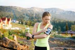 Femme sportive avec l'ami à l'aide du téléphone intelligent dans le parc Photo libre de droits