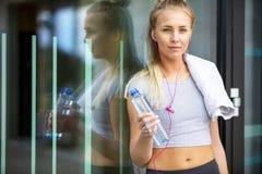 Femme sportive avec la bouteille d'eau se penchant contre le mur de verre Photo libre de droits