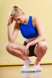 Femme sportive bouleversée sur l'échelle de poids Photo libre de droits