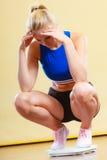 Femme sportive bouleversée sur l'échelle de poids Photographie stock libre de droits