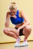 Femme sportive bouleversée sur l'échelle de poids Photo stock