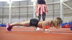 Femme sportive convenable de jeunes dans des vêtements de sports faisant des pousées banque de vidéos