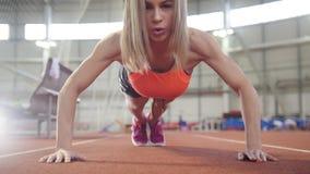 Femme sportive dans des vêtements de sports faisant des pousées dans la salle de gymnastique clips vidéos
