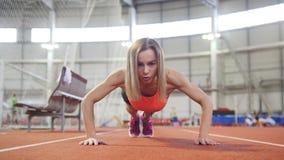 Femme sportive dans des vêtements de sports faisant des pousées banque de vidéos