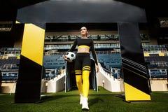 Femme sportive sportive dans les vêtements de sport avec du ballon de football dans les mains sur le stade image libre de droits