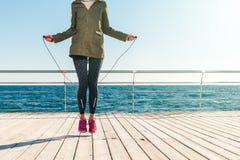 Femme sportive dans une veste et corde de sauts d'espadrilles dans le mornin Photo libre de droits
