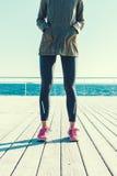 Femme sportive dans une veste et des espadrilles se tenant décembre en bois Photo libre de droits