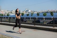 Femme sportive de brune courant sur le pont pr?s de la rivi?re L'espace pour le texte photos libres de droits