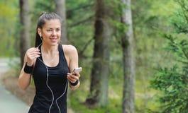 Femme sportive de forme physique saine de mode de vie avec l'écouteur pulsant dedans photographie stock