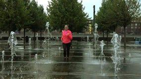 Femme sportive de jeune métis courant sous la pluie près des fontaines de parc de ville, tir superbe de mouvement lent clips vidéos