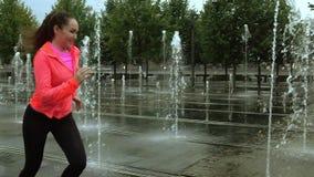 Femme sportive de jeune métis courant sous la pluie près des fontaines de parc de ville, vidéo animée lente superbe banque de vidéos