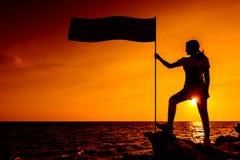 Femme sportive de silhouette sur la falaise Photo stock