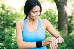 Femme sportive de sourire à l'aide de la montre intelligente dehors photos libres de droits