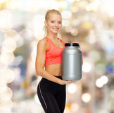 Femme sportive de sourire avec le pot de protéine Photo stock