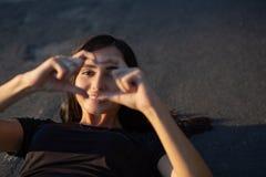 Femme sportive de sourire faisant le symbole de coeur à partir de ses doigts au stade L'espace pour le texte image stock