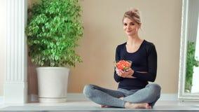 Femme sportive de sourire posant la séance dans le plat de participation de position de lotus avec de la salade de légume frais clips vidéos