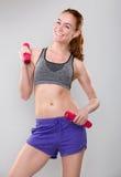 Femme sportive de sourire tenant des poids Photographie stock libre de droits