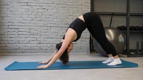 Femme sportive de tapis de yoga jeune ?tirant la hanche, muscles de tendon, muscles de jambe ? l'int?rieur dans un gymnase ?tirag banque de vidéos