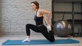 Femme sportive de tapis de yoga jeune ?tirant la hanche, muscles de tendon, muscles de jambe ? l'int?rieur dans un gymnase ?tirag clips vidéos