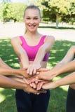 Femme sportive empilant des mains avec des amis Image stock