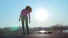 Femme sportive faisant des exercices pendant le lever de soleil ou le coucher du soleil fille folâtre sur la berge clips vidéos