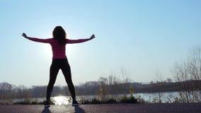 Femme sportive faisant des exercices pendant le lever de soleil ou le coucher du soleil fille folâtre sur la berge banque de vidéos