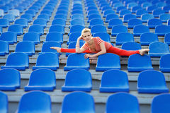 Femme sportive faisant les fractionnements sur les sièges du stade photographie stock libre de droits