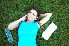 Femme sportive gaie écoutant la musique sur la pelouse photos libres de droits