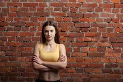 Femme sportive grave sur le fond de mur de briques Images stock