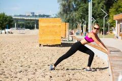 Femme sportive mûre dans des trains de maillot de bain sur la plage photographie stock libre de droits
