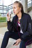 Femme sportive mangeant la barre de protéine tandis que musique de écoute sur des étapes photo stock