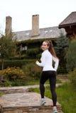 Femme sportive mince courant en haut Belle fille sur la traînée de formation dans les guêtres et des espadrilles Maisons en bois  Images stock