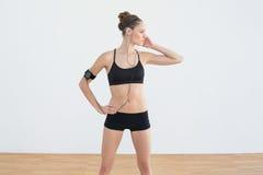 Femme sportive modifiée la tonalité écoutant la musique tout en posant dans les vêtements de sport Photographie stock libre de droits