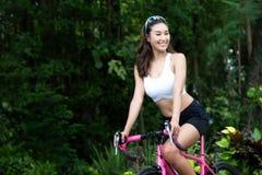 Femme sportive pratiquant sur la bicyclette dans le jardin sport photos stock