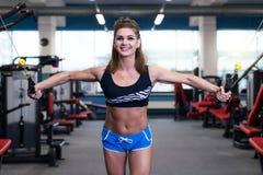 Femme sportive sexy faisant l'exercice de forme physique de puissance au gymnase de sport Belle fille établissant dans le gymnase Photographie stock libre de droits