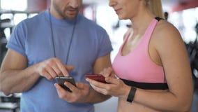 Femme sportive synchronisant le programme avec son entraîneur pour établir plus souvent banque de vidéos