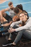 Femme sportive tenant la bouteille tout en se reposant près des équipiers et regardant l'appareil-photo Photographie stock libre de droits