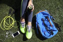 Femme sportive tenant le jus vert se reposant sur l'herbe Photo libre de droits